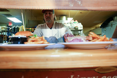Joe Petrunti serves up two dinners at The Village Cafe and Bistro.  Photo by John Fitts