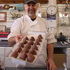 HOLLY PELCZYNSKI - BENNINGTON BANNER Ken Monte, chocolatier at the Village Chocolate Shoppe holds out chocolate covered, liquor filled strawberries, which will be featured for Valentines Day at the Shop on Main St. in Bennington.