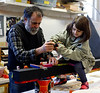 HOLLY PELCZYNSKI - BENNINGTON BANNER Village School of North Bennington Kindergartner, Fiona Clark drills decorated wood into a large post on Monday afternoon with the help of Matthew Perry, owner of the VT Arts Exchange. Once the piece is finished it will be placed in the school yard of the Village School of North Bennington.