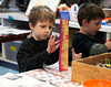 HOLLY PELCZYNSKI - BENNINGTON BANNER Village School of North Bennington Kindergartner, Henry Kane paints a block of wood and decorates it before adding it to a student created scupture that  will be placed in the school yard of The Village School of North Bennington once it is finished.