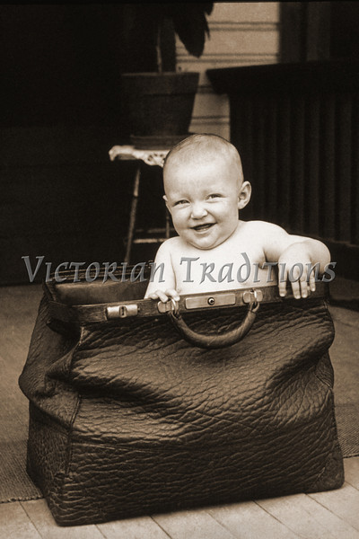 """Baby in doctor's medical bag - a vintage photo. (To purchase prints or downloads, click on the """"Buy"""" or shopping cart button above the image; then choose """"This Photo"""", followed by clicking on the 'Prints', 'Merchandise', or 'Downloads' tab. Your purchased prints & downloads will NOT have """"Victorian Traditions"""" watermark.)"""