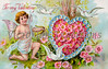 "Vintage Valentine illustration (circa 1910) -  a cupid with a bow and arrow next to heart-shaped flower wreath, with three white dove flying. Greeting says, ""To my Valentine"""