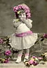 Hand-tinted vintage photograph of a shy little girl in lacy dress, and with flowers in her hair - circa 1900