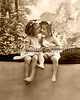 Best Friends. A vintage photograph of two little girl friends, cheek-to-cheek, hugging, and holding hands - circa 1900