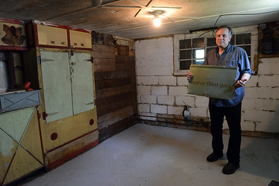 Tania Barricklo-Daily Freeman Frank Basile stands in the basement of the cottage kit he restored where he found vintage signs used as insulation.The entire basement was covered with board as seen on the left, which he removed, uncovering the signs and pieces of sign.