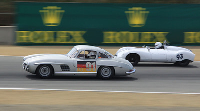 The 1955 Mercedes 300SL Gullwing Coupe driven by Alex Curtis passes a 1955 Cooper Type 39 Bobtail driven by David Brown exiting turn 4.