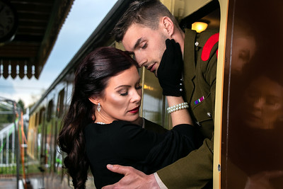 Vintage sad couple, man in uniform, woman in black dress, holding each other goodbye at train station as train departs