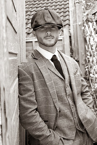 Handsome English gangster leaning on brick wall in back streets of birmingham
