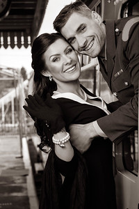 Vintage couple, man in uniform, woman in black dress holding each other on train, smiling and looking at camera.
