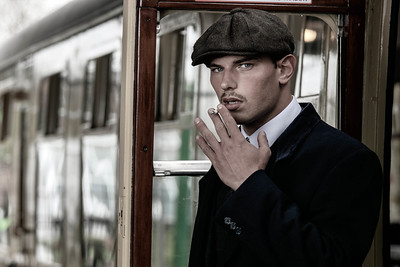 Handsome English gangster smoking at railway station with train in the background