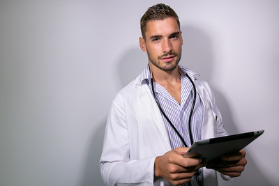 Good looking doctor wearing lab coat holding tablet and looking at camera on isolated background