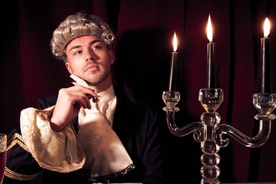 Portrait of young man dressed in regency costume and wig sitting at writing desk.