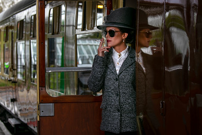 Beautiful female in vintage 1920s costume smoking cigarette while leaving train at train station