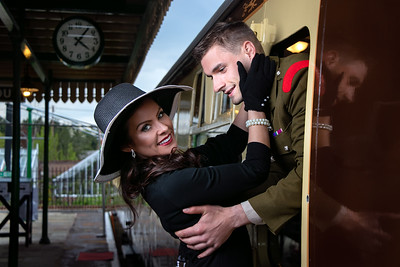 Vintage couple, man in uniform, woman in black dress and hat holding onto each other at train station as train departs
