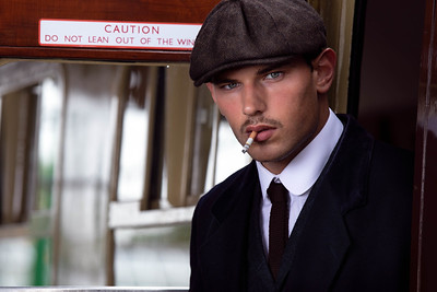 Handsome English gangster with cigarette leaving train at railway station.