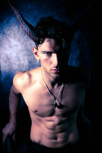 Sexy shirtless male devil with horns and muscular body showing pecs and abs looking at camera
