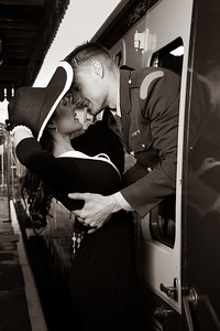 Vintage couple, man in uniform, woman in black dress, kissing goodbye at train station as train departs