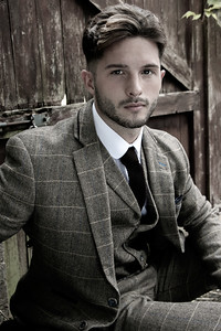 Handsome English gangster dressed in waistcoat and jacket sitting and looking at camera