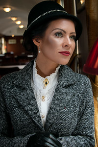 Portrait of beautiful female in 1920s costume with cloche hat sitting in vintage train carriage looking out of window