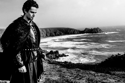 Knight with leather costume, fur cloak and sword standing in contemplation on cliff top with ocean in background.