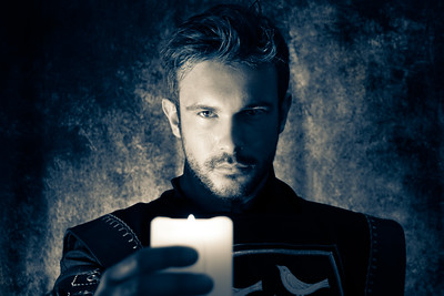 Atmospheric portrait of handsome knight with beard, looking at and holding candle up to camera while casting shadows