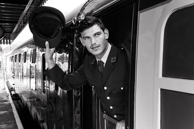 Handsome male American officer in vintage uniform hanging out of train and waving with his hat