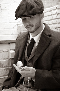 Handsome English gangster sitting in costume looking at pocket watch.