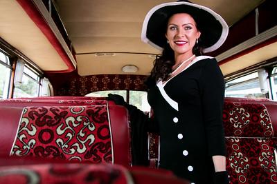 Vintage beautiful woman wearing hat standing inside retro bus