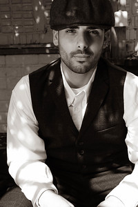 Handsome latino gangster dressed in waistcoat and jacket sitting and looking at camera