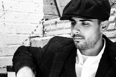 Handsome latino gangster dressed in shirt and jacket with flat cap sitting in front of white brick wall