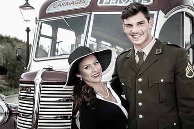 Vintage beautiful couple, woman wearing hat and man in ww2 uniform standing in front of retro bus, smiling