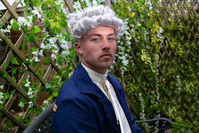 Portrait of handsome gentleman dressed in vintage costume standing in stately home garden