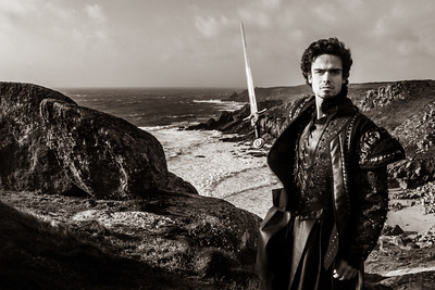 Black and white portrait of handsome knight holding sword and pointing to coastline in the distance