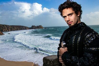 Bright portrait of handsome knight standing on castle balcony with blue skies and ocean in background