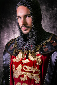Portrait of handsome medieval knight in suit of armour with beard and blue eyes looking at camera