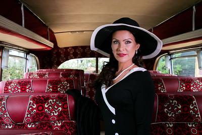 Vintage beautiful woman wearing hat sitting on retro bus