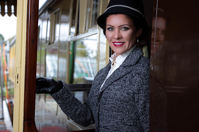 Beautiful female in 1920s costume with cloche hat leaving train at station and smiling at camera