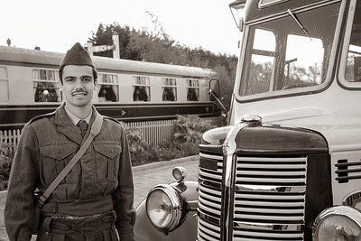WW2 soldier standing in front of retro bus with train station in background