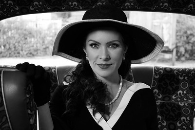 Vintage beautiful woman wearing hat sitting at the back of retro bus.
