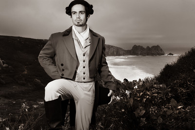 Portrait of handsome 18th century gentleman dressed in vintage costume, holding top hat with ocean in background