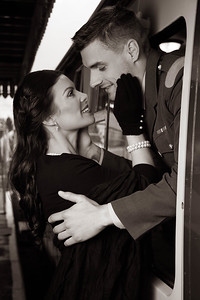 Vintage couple, man in uniform, woman in black dress, about to kiss goodbye at train station as train departs