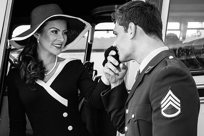 Vintage beautiful woman wearing hat is helped off retro bus by soldier in wwii uniform