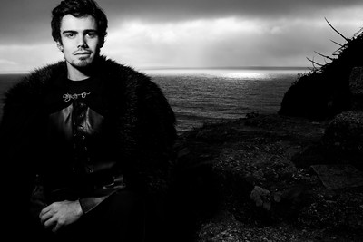 Portrait of handsome knight with goatee and fur coat looking at camera with ocean in background
