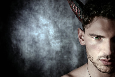 Half profile of sexy shirtless male devil with horns and room for copy