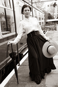 Portrait of beautiful vintage lady standing on platform with hat and umbrella