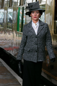 Beautiful english woman dressed in 1920s costume walking on railway platform with train in background