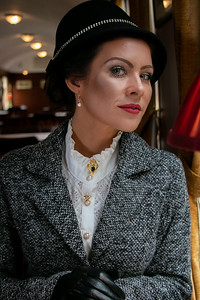 Portrait of beautiful female in 1920s costume with cloche hat sitting in vintage train carriage looking at camera