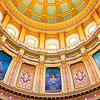 This image showcases an interior view of the beautiful Michigan State Capitol Dome, built in the late 1800's. It features paintings of muses, drawn from Greek and Roman mythology, all chosen to inspire Michigan citizens to achieve progress and prosperity. The dome rises 160 feet up, and was created to awe and inspire visitors.