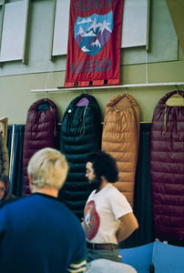 Bill Nicolai, wearing a Grateful Dead t-shirt, listens to Carol as she explains the finer points of custom sleeping bag construction to a potential customer. Feathered Friends bags hang on the back wall of our booth.