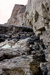 Larry leading out on a melted out, wet rocky pitch, where we had expected ice. Climbing hard rock wearing crampons was a uncomfortable experience.